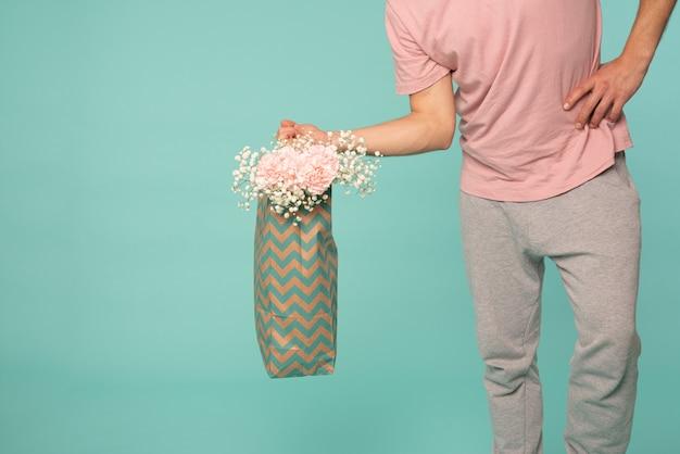 カジュアルな服装の若い男のトリミングされたfotが分離された花の買い物袋を保持しています。