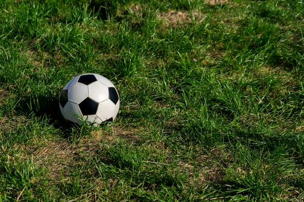 Fotball or soccer black and white ball on green grass background.