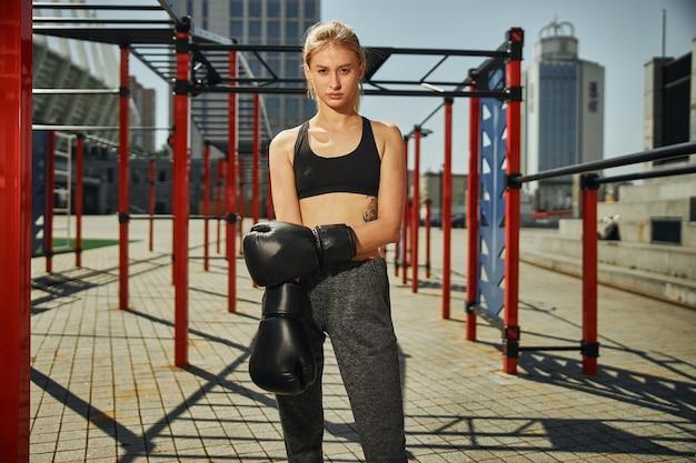 スポーツグラウンドでキックボクシングのトレーニングを練習しようとしている魅力的な女性の膝の上の写真