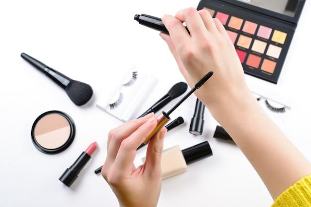 여자 손에 기초. 미용 미용 제품, 파운데이션, 립스틱, 아이섀도, 속눈썹, 브러쉬 및 도구가 포함 된 전문 메이크업 제품입니다.