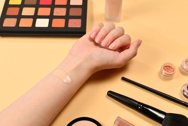 여자 손에 기초. 미용 미용 제품, 파운데이션, 립스틱, 아이 섀도우, 브러쉬 및 도구가 포함 된 전문 메이크업 제품입니다.