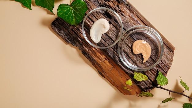 Образец основы, образец увлажняющего крема в чашках петри на деревянной доске с растениями. уход за кожей составляют продукты на цветном бежевом фоне. лабораторные исследования натуральной косметики. длинный веб-баннер.