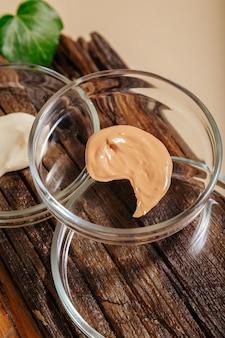Образец основы, образец увлажняющего крема в чашках петри на деревянной доске с растениями. уход за кожей составляют продукты на цветном бежевом фоне. лабораторные исследования натуральной косметики.