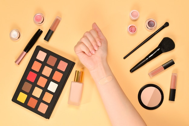 Foundation on woman hand. professional makeup products with cosmetic beauty products, foundation, lipstick,  eye shadows, brushes and tools.