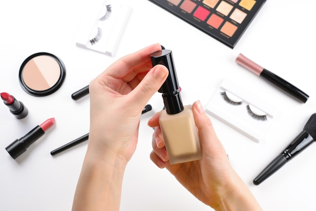 Foundation in woman hands. professional makeup products with cosmetic beauty products, foundation, lipstick,  eye shadows, eye lashes, brushes and tools.