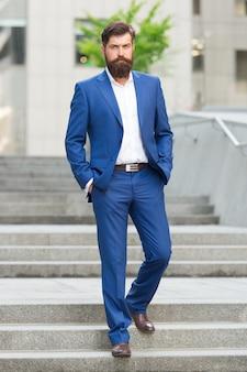 創業者の成功したビジネス。ビジネスの世界を征服する。あごひげを生やした男が仕事に行きます。近代都市のビジネスマン。就業日の始まり。成功への動機。サラリーマンは自信を持って階段を踏みます。