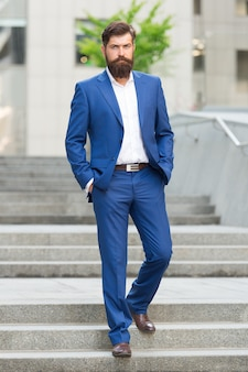 Founder successful business. conquer business world. bearded man going to work. business man in modern city. beginning of working day. motivated for success. office worker confidently step on stairs.