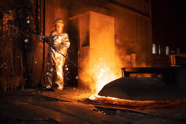 Foundry worker in aluminized protective fire suit checking temperature of molten iron in furnace, industrial steel production and metallurgy.
