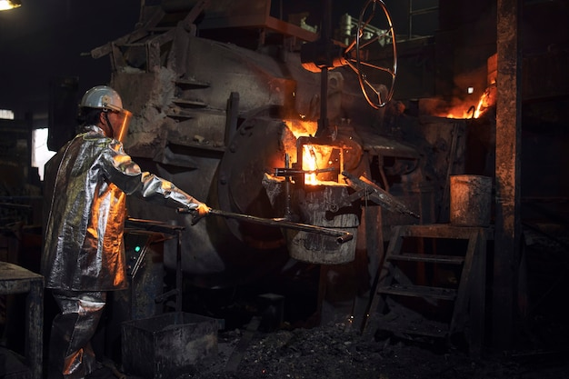 Foundry worker pouring hot steel into bucket for metal casting.