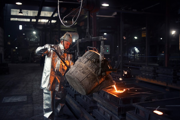 Foundry worker pouring liquid steel into molds.