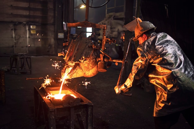Foundry worker in protective suit and hardhat filling mold with hot molten iron to make parts for industry.