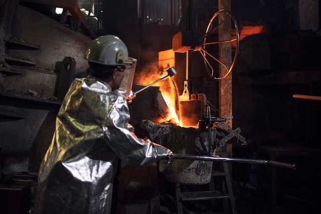 Foundry worker in protective suit operating hot industrial furnace with liquid molten iron.