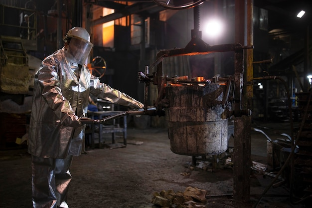 Foundry worker working with hot liquid iron in smelter for steel production and metallurgy.