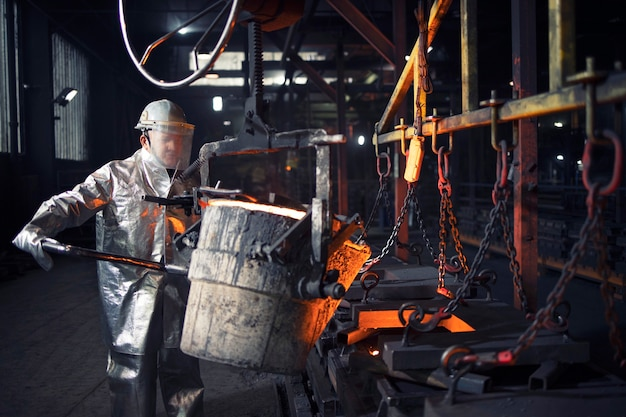 Foundry worker working with hot steel, metallurgy and heavy industry.