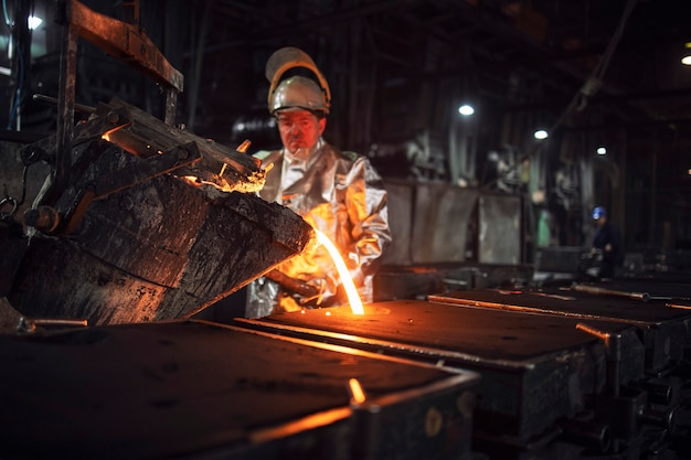 Foundry workman pouring molten iron into molds for steel production, heavy industry and metallurgy process.