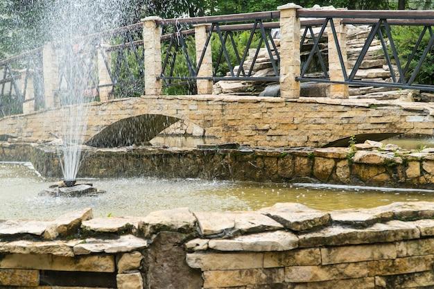 Фонтан и мостик из каменной плитки в парке. декоративный пруд на открытом воздухе