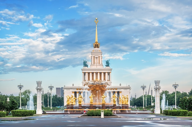Fountain friendship of peoples with golden statues of girls and the central pavilion with a high spire on the territory of vdnh in moscow on a summer evening