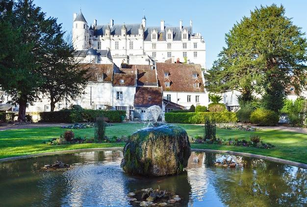 Весной общественный парк с фонтаном в городе лош, франция, и замок, построенный в ix веке позади.