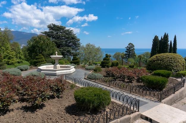 Фонтан в саду перед белым ливадийским дворцом в ялте, крым на красивом фоне с морем и облаками