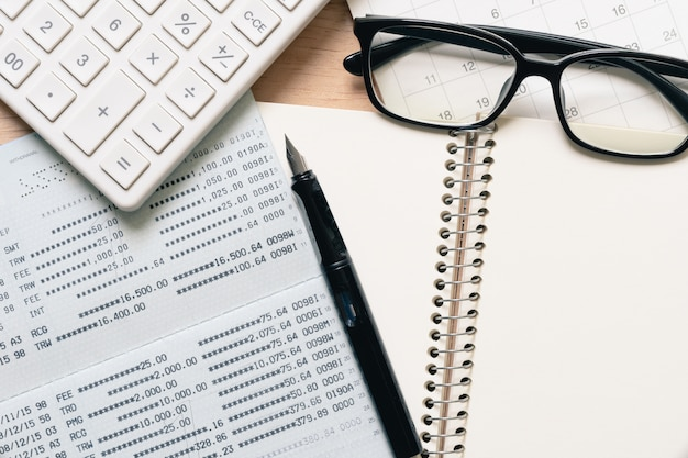 A fountain pen and black eye glasses spectacles is placed on a calendar.
