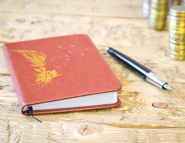 Fountain pen, coins and notebook on a wooden table.