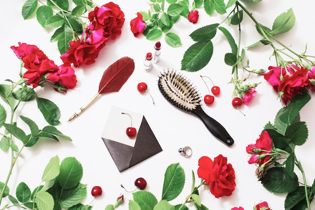 Fountain pen, hairbrush, lipstick, ring, ripe cherries, small envelopes, roses with green leaves lay on white background. flat lay, top view. flower frame. female boudoir. workplace