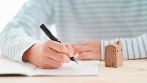 Fountain pen holding by man with small ceramic home model on desk