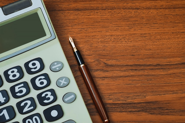 Fountain pen or ink pen with calculator on wood