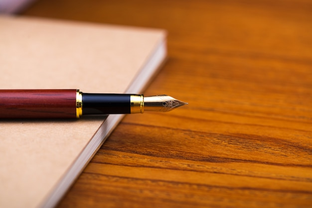Fountain pen or ink pen with notebook paper on wood