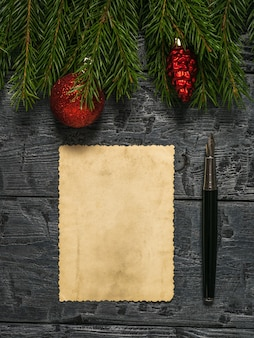 A fountain pen, a sheet of old paper, ornaments and spruce branches on a wooden background. a letter requesting a gift.