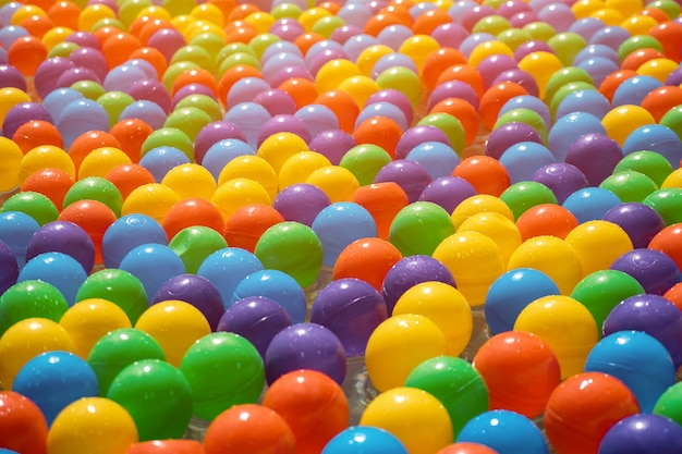 Fountain or pool for children. colorful small plastic balls in water, closeup view. outdoor free entertainment for kids.