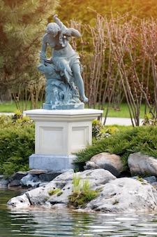 호수 근처 공원에서 여자의 동상과 분수