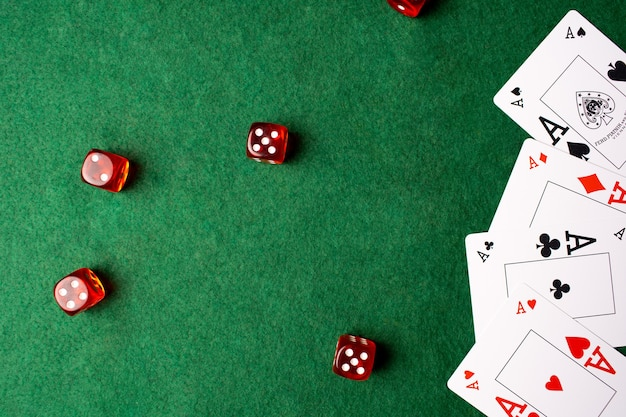 Four aces and dice on green casino table