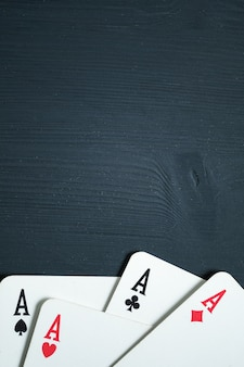 Four aces lies on a black wooden background.