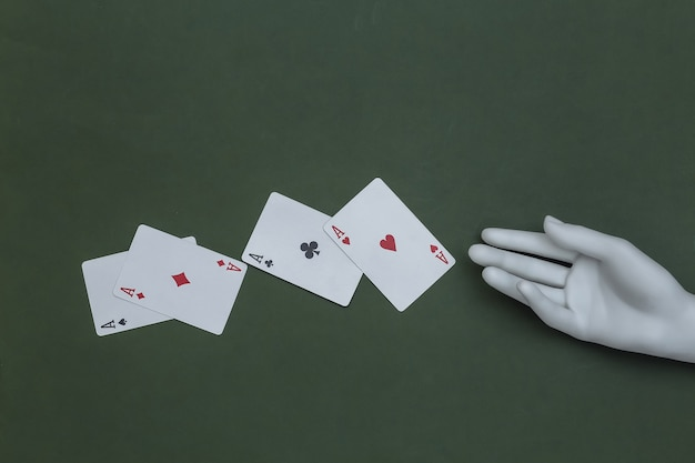 Four aces and mannequin hand on green background