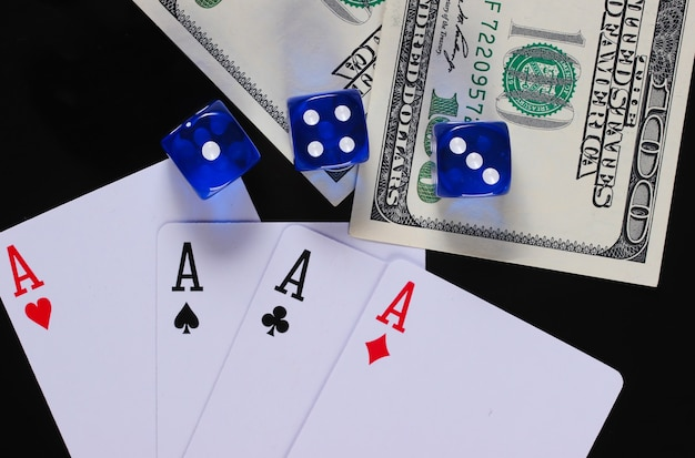 Four aces with dices and hundred dollar bills on a black surface. gambling
