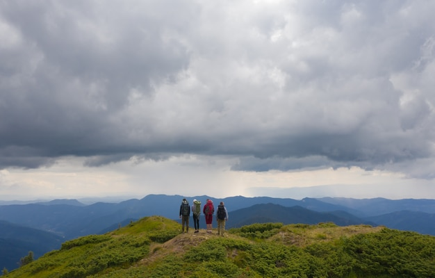 The four active people standing on the mountain against beautiful clouds