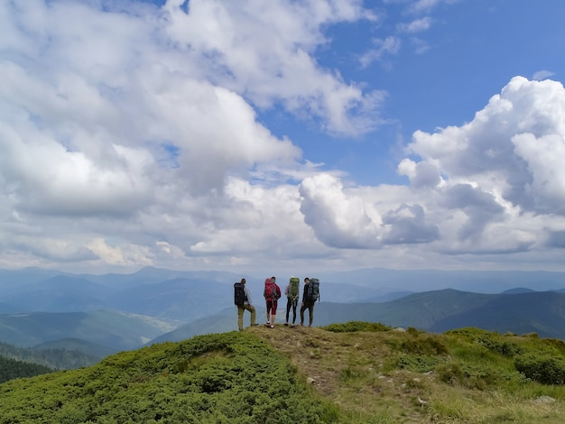 The four active people standing on the picturesque mountain
