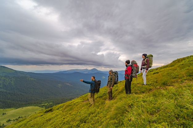 The four active people with backpacks standing on the green mountain