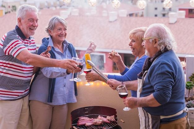 은퇴 한 4 명의 현역 선배가 집 테라스에서 즐거운 시간을 보내며 바베큐 요리를하고 있습니다. 휴가 및 관계 사람들 개념