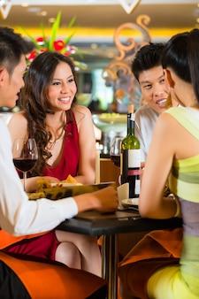 우아한 클럽 레스토랑이나 호텔에서 저녁 식사를하는 4 명의 아시아 중국 비즈니스 사람들
