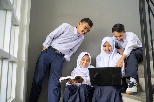 교복을 입은 4 명의 아시아 청소년이 함께 노트북을 사용하여 공부합니다.
