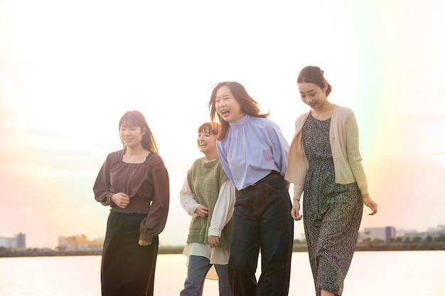 Четыре азиатские молодые женщины счастливо разговаривают в сумерках