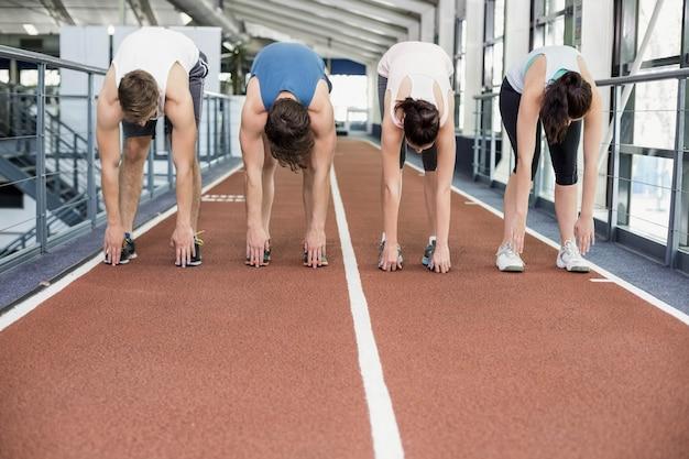 Четыре спортивные женщины и мужчины, растягивающиеся на беговой дорожке
