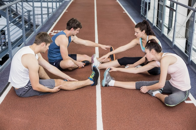 Four athletic women and men stretching on running track
