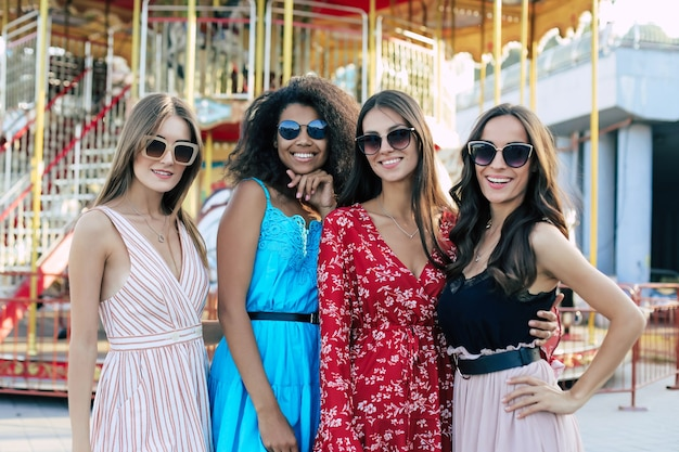 4人の魅力的な女性が都会の背景でポーズをとり、お互いの腰を抱きしめ、大きく笑い、若さを楽しんでいます