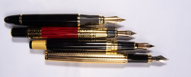 Four beautiful fountain pens in detail on white surface, top view.
