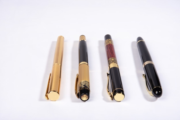 Four beautiful fountain pens in detail on white surface