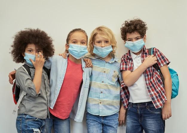 Четыре красивых многонациональных ребенка в защитных масках, глядя в камеру, позируют