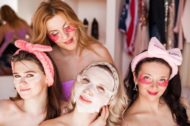 Четыре красивые молодые женщины в розовых полотенцах с косметическими повязками на голове позируют перед камерой с пятнами под глазами и в тканевой косметической маске